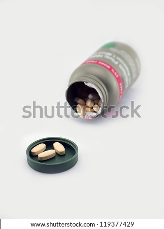 Spilling white Calcium Pills - stock photo