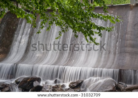 spillway with green leaves outlining top of image