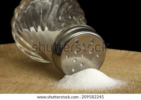 Spilt salt and salt shaker on wood with black background - stock photo