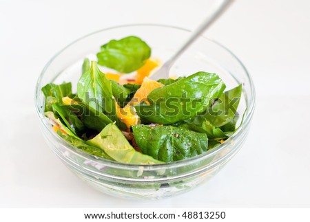 Spinach and orange salad in the bowl - stock photo