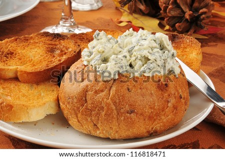 Spinach arrtichoke parmesan dip in a bread bowl with italian toast