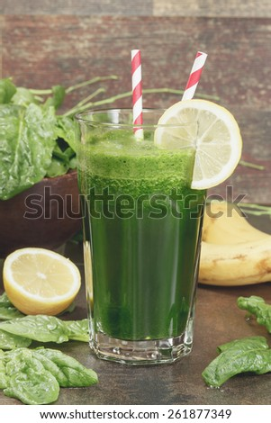 Spinach Banana Smoothie.  Healthy refreshing green smoothie made of fresh  spinach, lemon  and banana in a glass on dark wood . Macro photograph with shallow depth of field. - stock photo