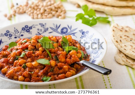 Spinach chickpea curry, fresh and healthy, with herbs and lebanese bread - stock photo