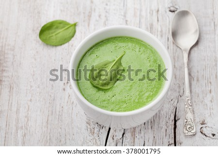Spinach cream soup in bowl on white rustic table - stock photo