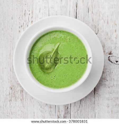 Spinach cream soup in bowl on white rustic table, top view - stock photo