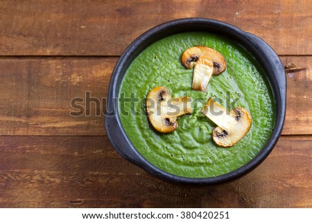 Spinach cream soup in clay bowl on wooden background. Vegetarian food. Top view - stock photo