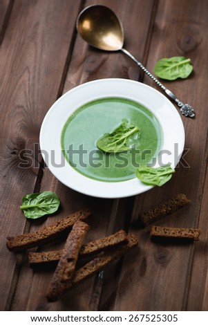 Spinach cream-soup with croutons over dark wooden background