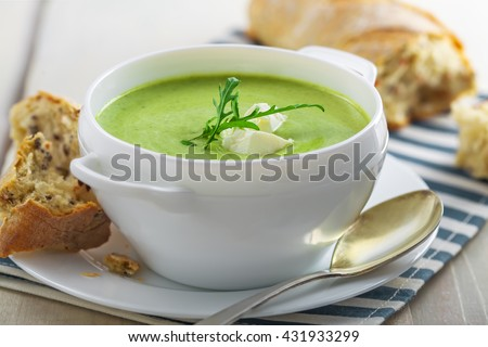 Spinach cream soup with rye bread on a table. Traditional European food for lunch. Close-up shot. - stock photo