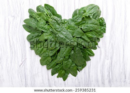 Spinach in heart shape on a background - stock photo