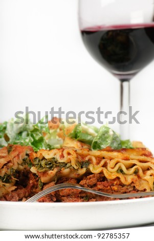 Spinach lasagna dinner with ceasar salad and red wine - stock photo