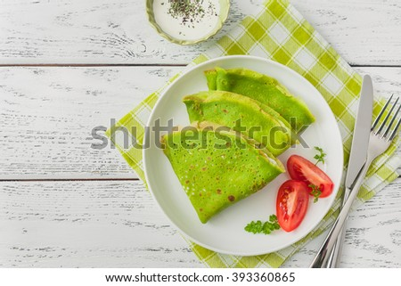 Spinach pancakes on wooden background.