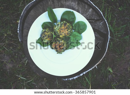 Spinach pancakes on wooden stump outdoors. Vintage toning. - stock photo
