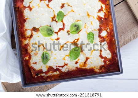 Spinach, ricotta and bacon lasagna topped with mozzarella cheese - stock photo