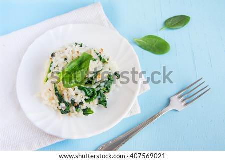 Spinach risotto with white rice on plate, italian vegetarian cuisine, close up top view