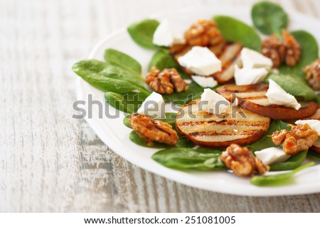 spinach salad, roasted pears, white cheese and caramelized walnuts on a white plate on a wooden background - stock photo