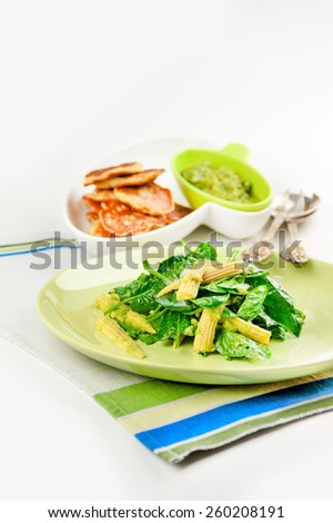 spinach salad with corn and avocado; pancakes with corn - stock photo