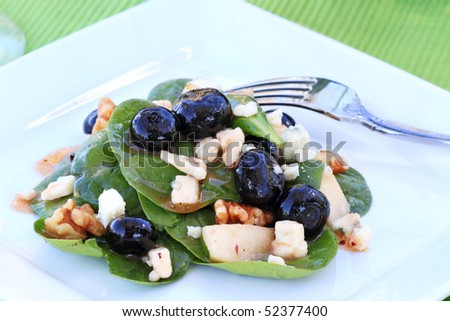 Spinach salad with gorgonzola cheese, walnuts, pears, blueberries and a raspberry vinaigrette. - stock photo