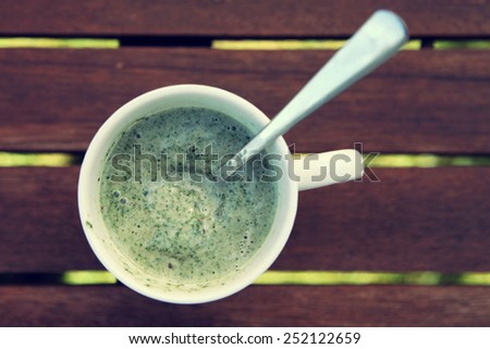 Spinach smoothie on wooden background - stock photo