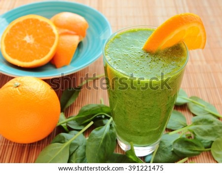 Spinach smoothie with fresh orange in a glass - stock photo