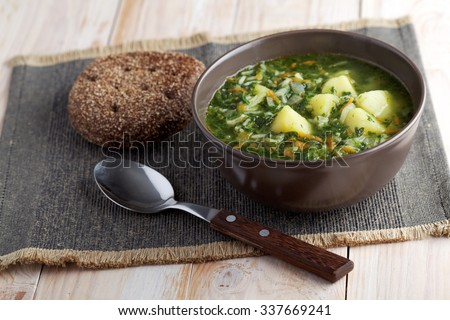 Spinach soup and rye bread on a rustic table - stock photo