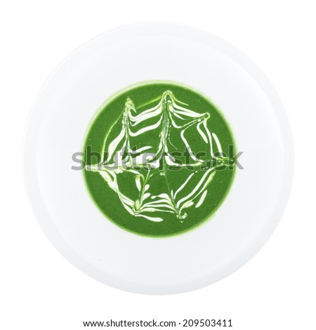 Spinach soup decorated with sour cream isolated on white background. Clipping path - stock photo