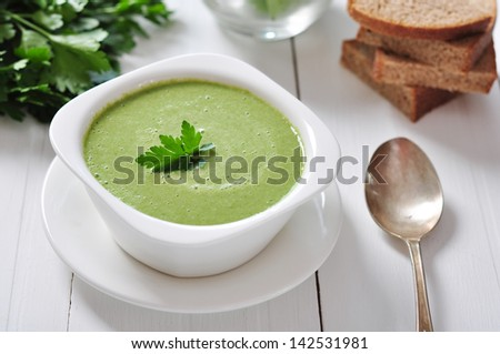 spinach soup in a bowl on a wooden background - stock photo
