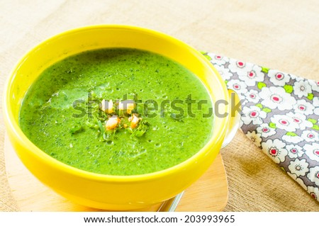 Spinach soup in yellow bowl - stock photo
