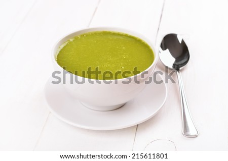 Spinach soup on wooden table - stock photo