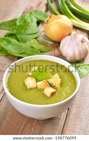 Spinach soup with croutons on wooden table - stock photo