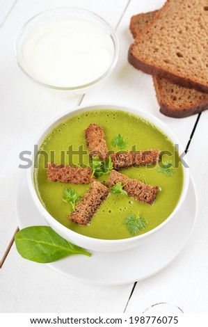 Spinach soup with dried crusts on wooden table - stock photo