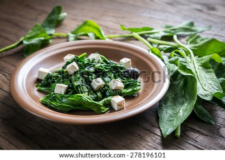 Spinach with cheese, olives - stock photo