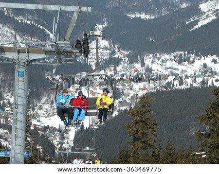SPINDLERUV MLYN, CZECH REPUBLIC - MARCH 24, 2006: Skiers riding a chair lift at a ski area. Behind them is visible panorama ski resort. - stock photo