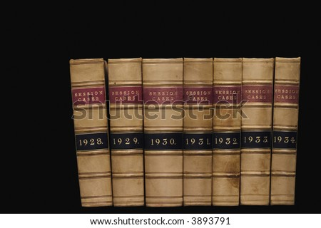 Spines of law reports against a black background - stock photo