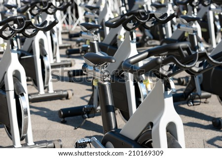 Spinning bikes / Large group of aluminum spinning bikes outdoors - stock photo