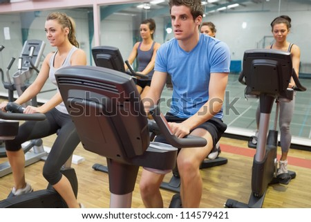 Spinning class riding on a exercise bikes in gym - stock photo