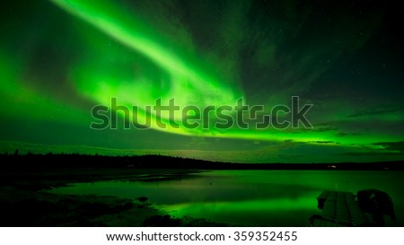 Spinning Lights - Bands of bright northern lights spinning across the starry night sky over a lake.  - stock photo