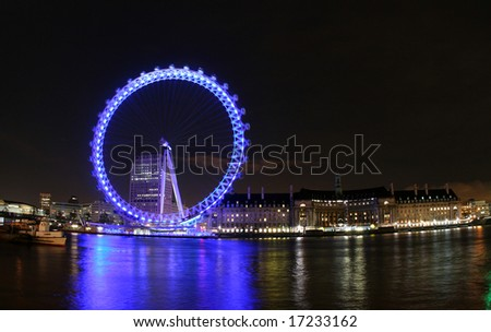 Spinning London Eye and view of the South bank at night. - stock photo