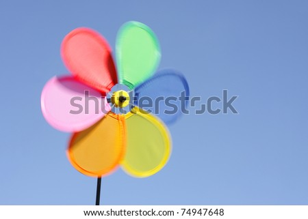 Spinning pinwheel toy against blue sky