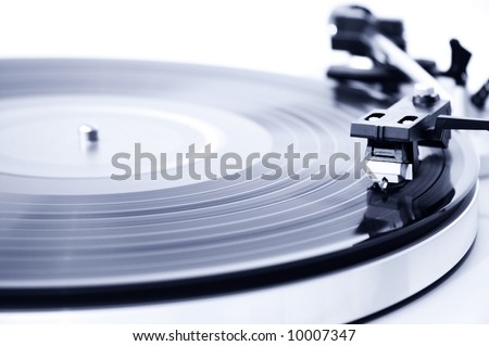 Spinning record player. Focus on the needle head. - stock photo