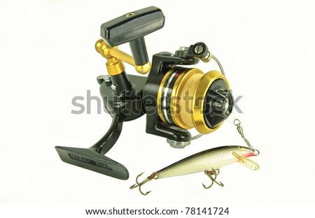 Spinning Reel:  A well-used spin casting reel is rigged with an artificial minnow. - stock photo