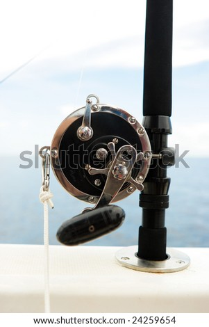 Spinning rod on the yacht board - stock photo