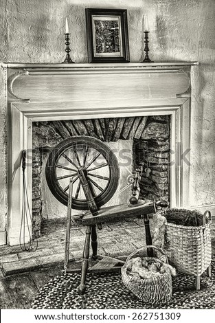 Spinning Wheel in Front of a Fireplace with Baskets - stock photo