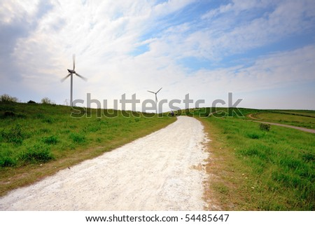 Spinning windmill in green landscape with white path and cloudy sky