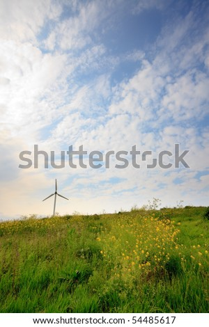 Spinning windmill in green landscape with yellow flowers and cloudy sky