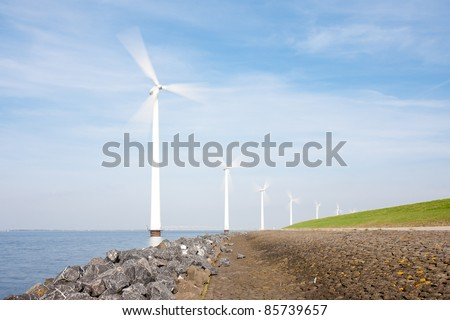 Spinning windturbines standing in the sea photographed with long exposure - stock photo