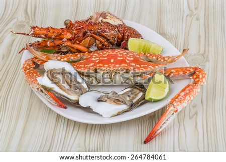 Spiny lobster, crab and oyster on the bowl with lime - stock photo