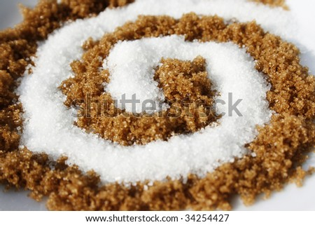 Spiral arrangement with sweet white and brown sugar - stock photo