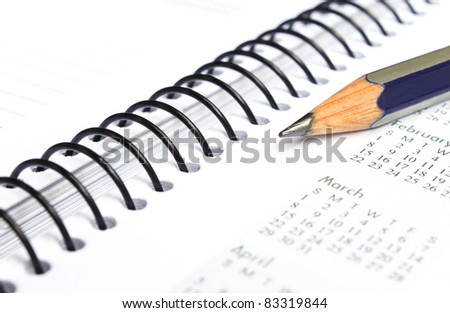 Spiral bound note book with writing pencil - stock photo