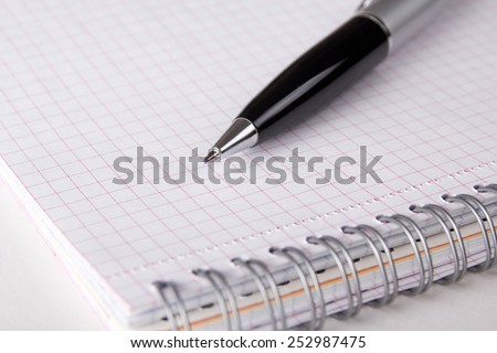 spiral note book with checked pages and pen