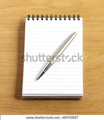 spiral notebook and pen on wooden desk - stock photo